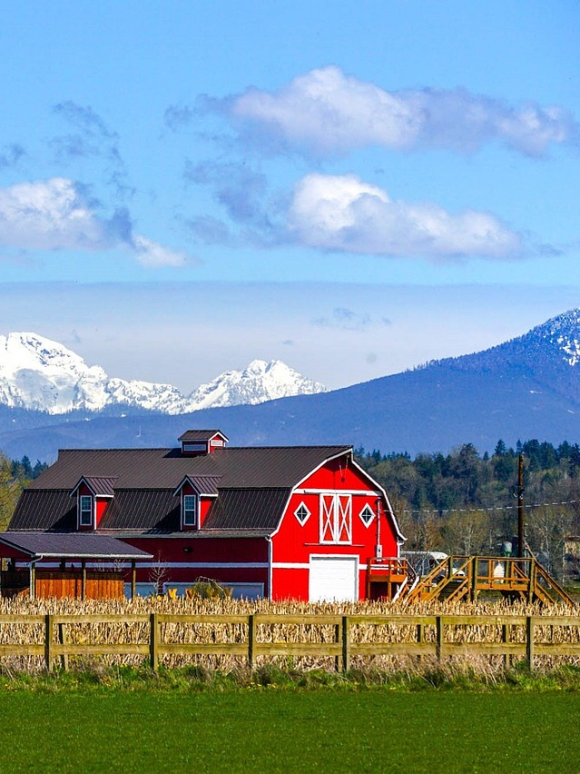Red farm barn in front of mountains
