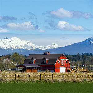 Large red barn at the foothills of mountains