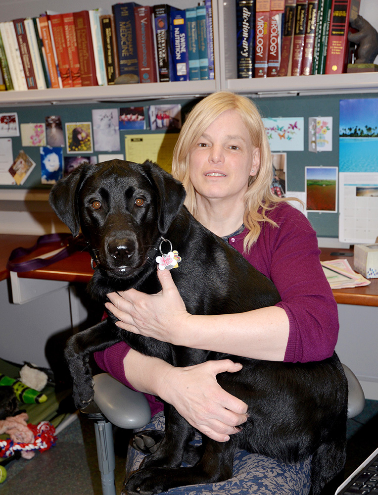 Dr. Stephanie Rossow with Bunker, her black lab, in her office at the Veterinary Diagnostic Laboratory
