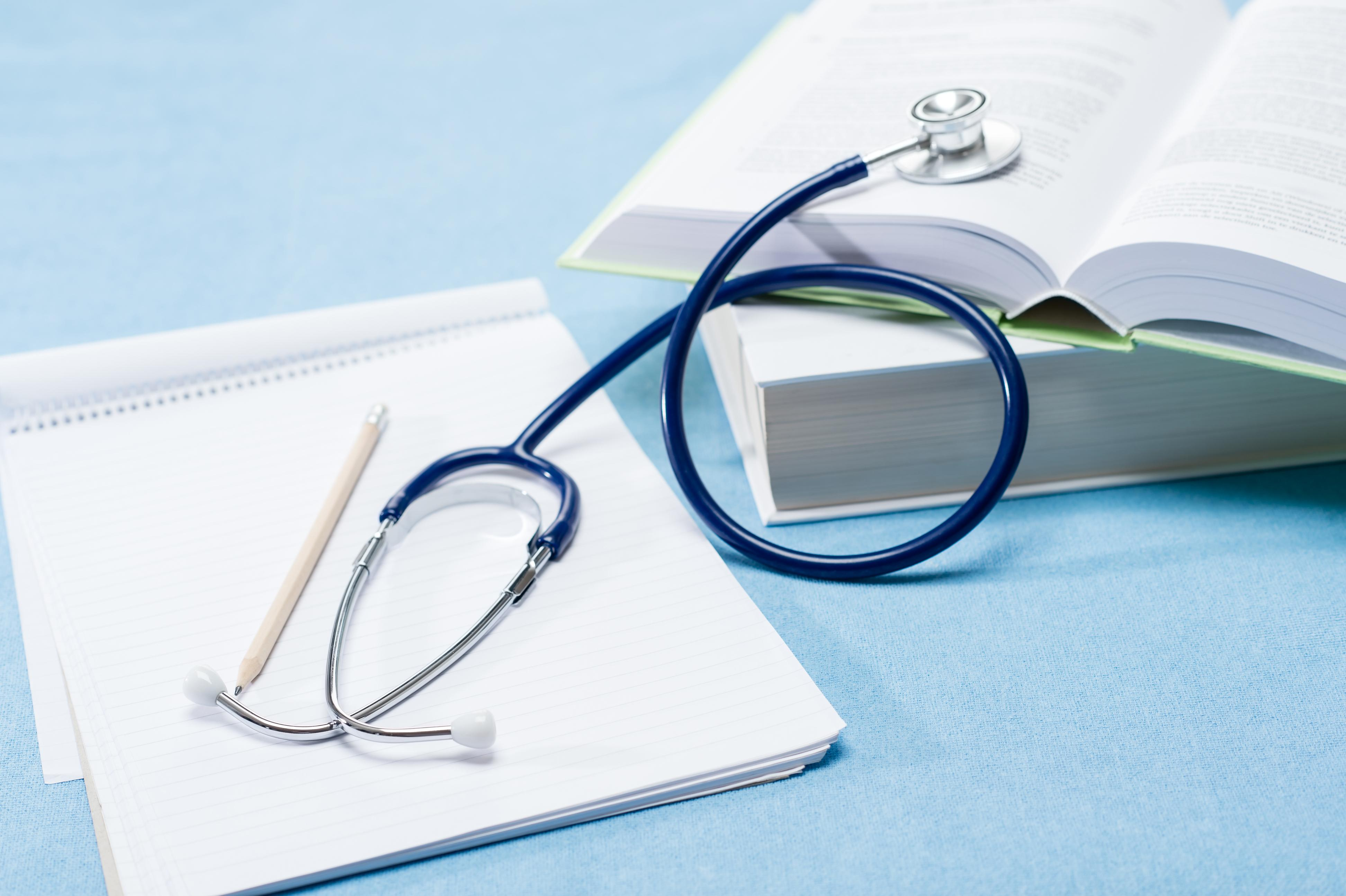 A stethoscope and textbooks