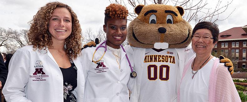 Two veterinary students and staff member pose for photo with Goldy Gopher