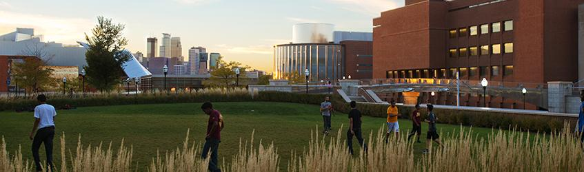 students on the student union lawn at sunset with the minneapolis skyline in the background